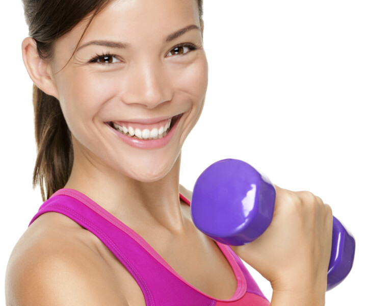 Fitness sport girl smiling happy. Fitness woman lifting dumbbells strength training biceps doing curls. Mixed Caucasian and Asian fitness model portrait isolated on white background.