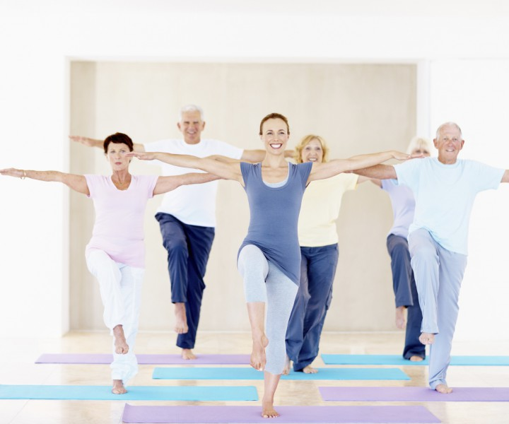 Portrait of an attractive woman leading a group of seniors in a yoga class